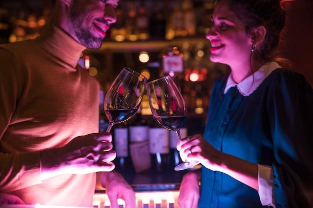 Gelukkige mens die glazen wijn met vrolijke vrouw klettert