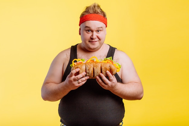 Gelukkige mens die hamburger voorbereidingen treft te eten