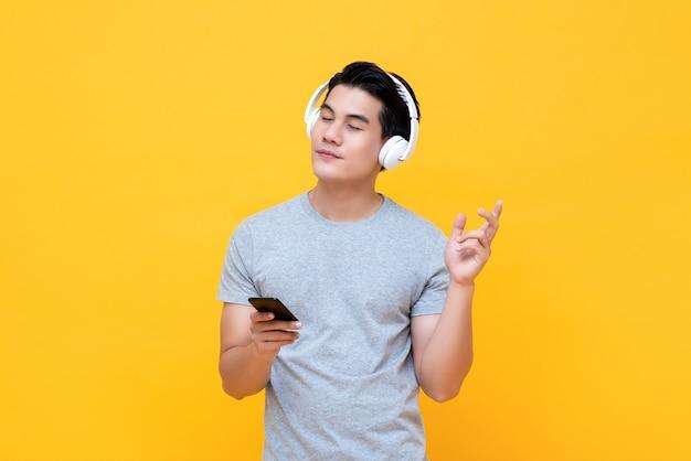 Gelukkige mens die hoofdtelefoons draagt die aan muziek van smartphone met gesloten oog luisteren