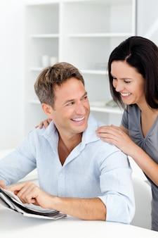 Gelukkige mens die iets op de krant toont aan zijn meisje