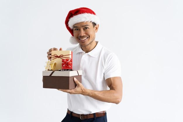 Gelukkige mens die kerstmanhoed draagt en giftdozen toont