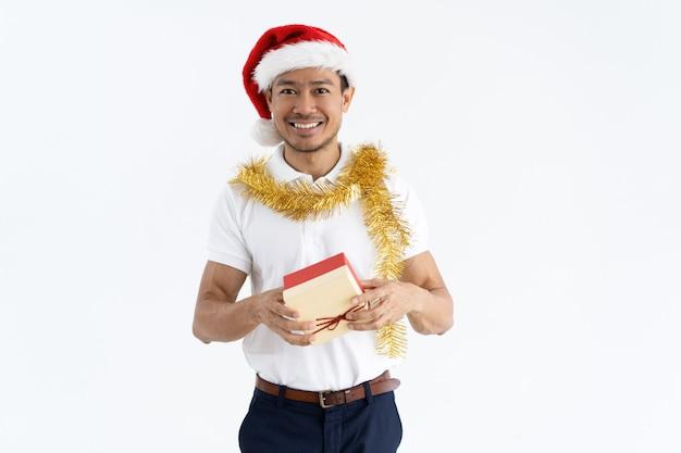Gelukkige mens die kerstmanhoed, klatergoud draagt en giftdoos houdt