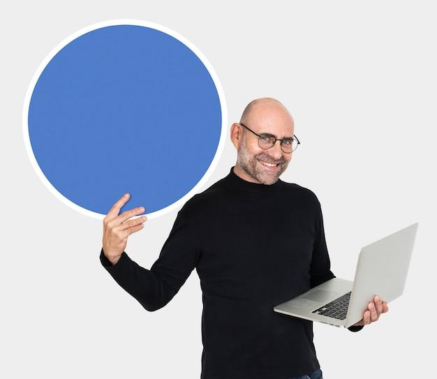Gelukkige mens die laptop draagt en een raad houdt