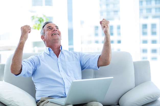 Gelukkige mens die omhoog terwijl het werken aan laptop kijkt