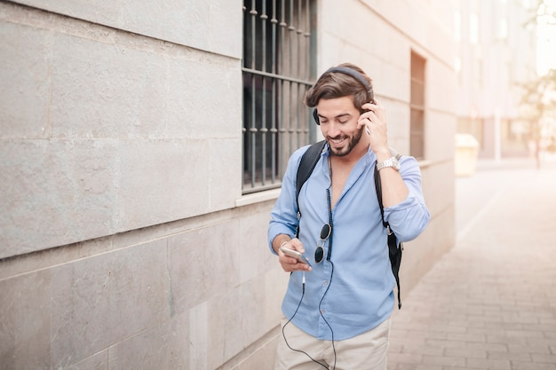 Gelukkige mens die op bestrating loopt die aan muziek luistert