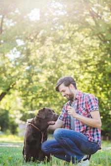 Gelukkige mens die pret met zijn hond in park heeft