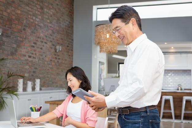 Gelukkige mens die tablet thuis gebruiken terwijl de zwangere vrouw aan laptop werkt