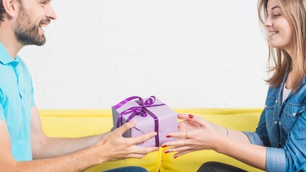 Gelukkige mens die valentijnskaartgift geeft aan zijn meisje