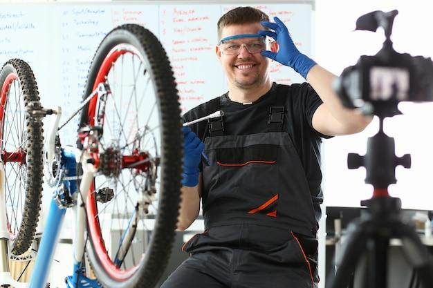 Gelukkige mens die veiligheidsbril aanpassen en dichtbij fiets zitten