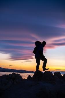 Gelukkige mens die zich op klip bevindt en landschapsmening bekijkt