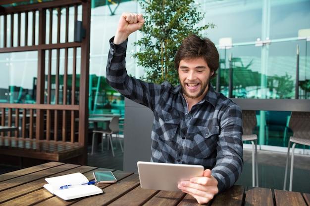 Gelukkige mens gebruikend tablet en vierende voltooiing in koffie