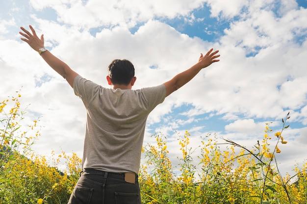 Gelukkige mens in aard van gele gebiedsbloem en heldere hemel witte wolk