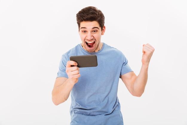 Gelukkige mens in toevallig t-shirt die zijn overwinning verheugen terwijl het spelen van online spelen op smartphone, die over witte muur wordt geïsoleerd