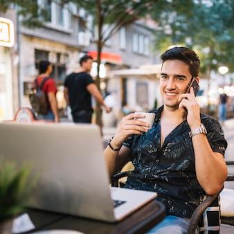 Gelukkige mens met kop van koffie die op cellphone spreekt