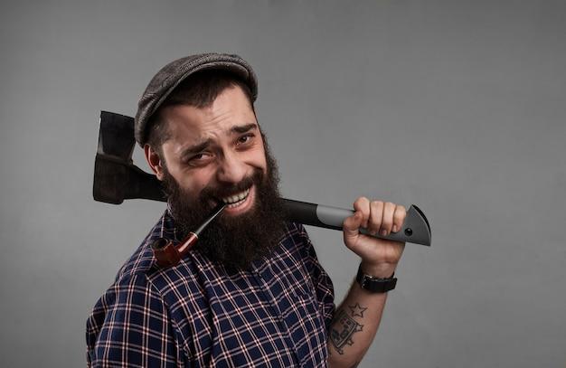Gelukkige mens met tabakspijp in mond en met in hand bijl. glimlachende aantrekkelijke kerel met baard op grijze achtergrond in studio. tevredenheid van het levensconcept.