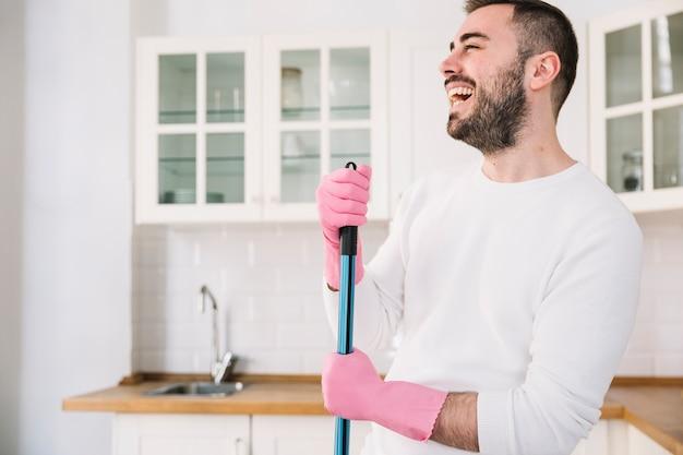 Gelukkige mens met zwabber op keuken