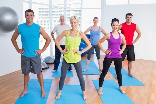 Gelukkige mensen die in gymnastiekklasse uitoefenen