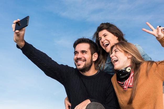 Gelukkige mensen die selfie op blauwe hemelachtergrond nemen