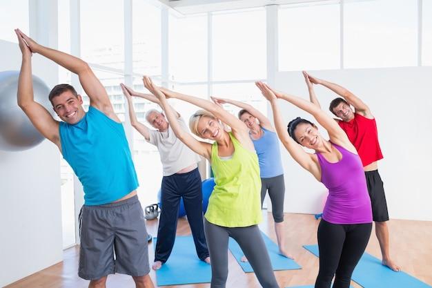 Gelukkige mensen die uitrekkende oefening in yogaklasse doen