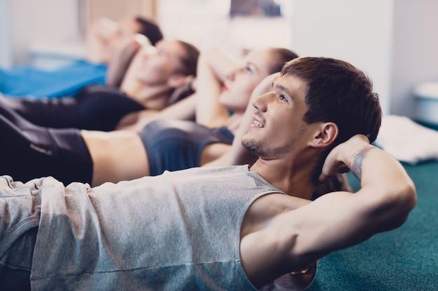Gelukkige mensen doen een oefening op een crunches liegen