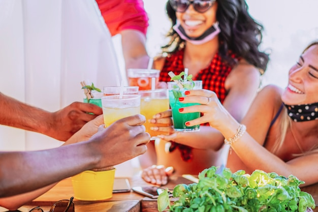 Gelukkige mensen juichen met drankjes en plezier maken