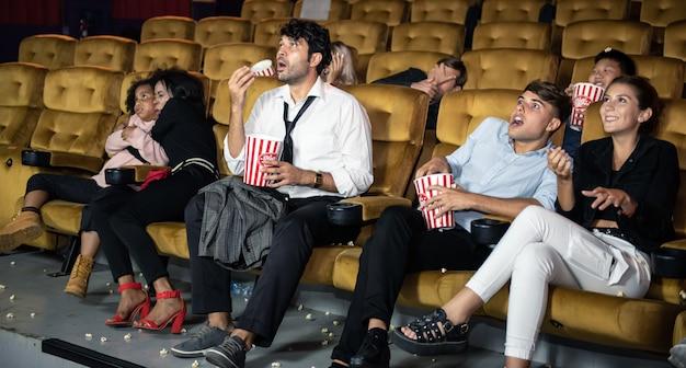 Gelukkige mensen kijken naar film met genieten in het theater.
