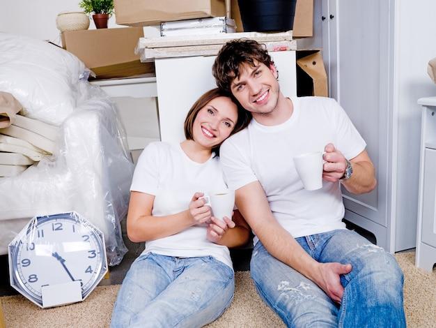 Gelukkige mensen zittend op de vloer met kopjes thee na verwijdering in het nieuwe huis en ontspannen