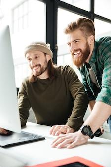Gelukkige mensencollega's in bureau die computer met behulp van. opzij kijken.