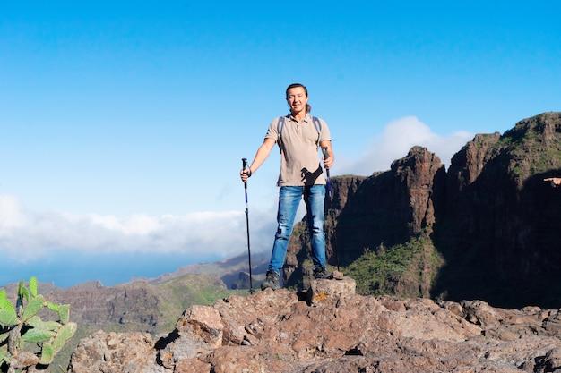 Gelukkige mensenreiziger van middelbare leeftijd die bij camera glimlachen terwijl status bovenop heuvel tegen blauwe hemel en mooi landschap