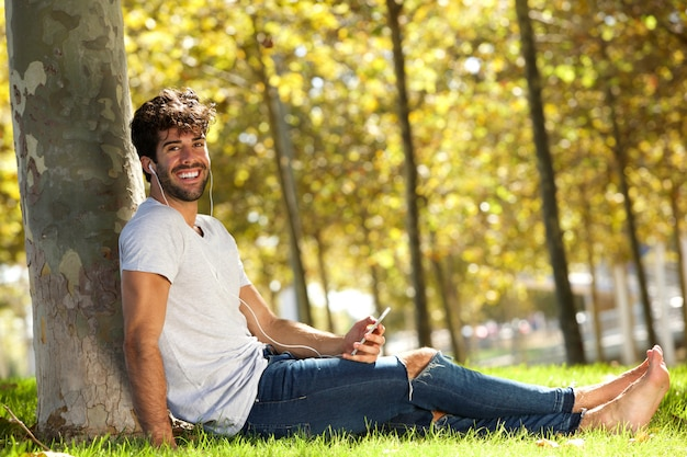 Gelukkige mensenzitting in gras met cellphone en hoofdtelefoons