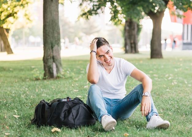 Gelukkige mensenzitting op gras in park