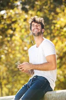 Gelukkige mensenzitting op muur in park met cellphone