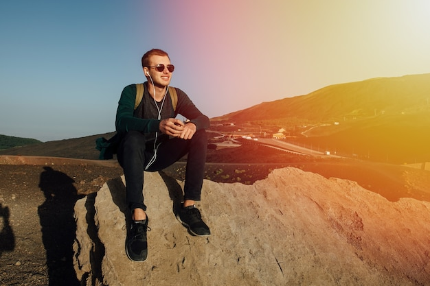 Gelukkige mensenzitting op rots en het luisteren aan muziek in hoofdtelefoons bij zonsondergang