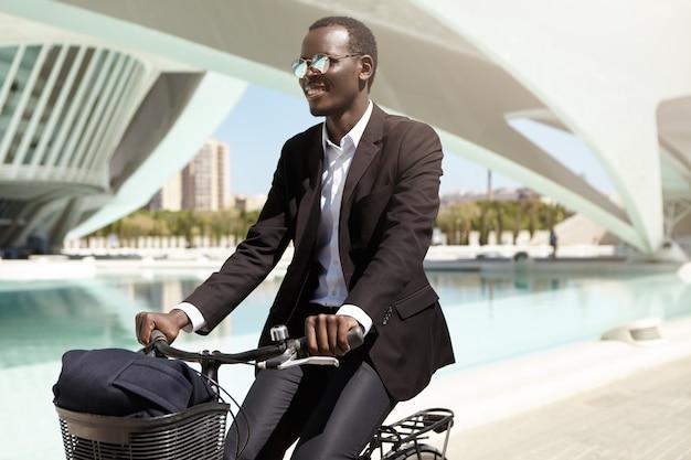 Gelukkige milieubewuste afro-amerikaanse werknemer in zwart formeel pak en zonnebril die de fiets kiest boven het openbaar vervoer of de auto om naar kantoor te gaan, genietend van een rit in een stedelijke omgeving