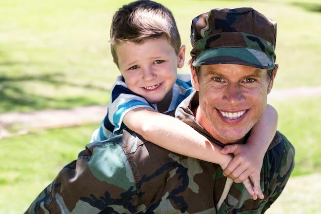 Gelukkige militair die op de rug aan zijn zoon geeft