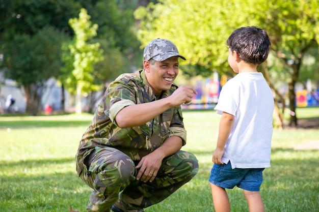 Gelukkige militaire vader die zoon ontmoet na zendingsreis. jongen lopen naar papa camouflage uniform dragen in park. familiereünie of het concept van thuiskomst