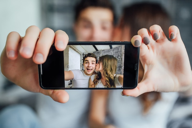 Gelukkige minnaar die de technologiesmartphone gebruikt voor selfie op het bed in de slaapkamer thuis