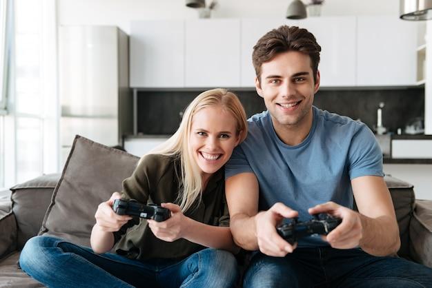 Gelukkige minnaars die camera kijken terwijl thuis het spelen van videospelletjes
