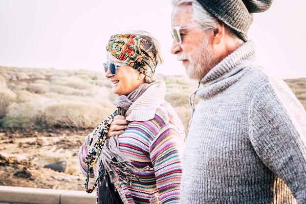 Gelukkige mode paar senior mensen in outdoor vrijetijdsbesteding samen in paar - koud seizoen en vrolijke vrouw met man in relatie - heldere witte lucht