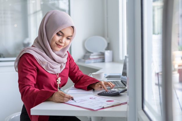 Gelukkige moderne aziatische moslim bedrijfsvrouw die aan bureau werkt.