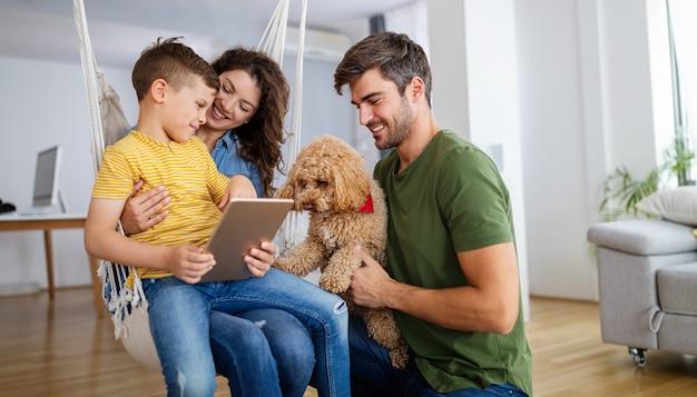 Gelukkige moderne familie die computer samen thuis gebruikt. technologie, mensenconcept.