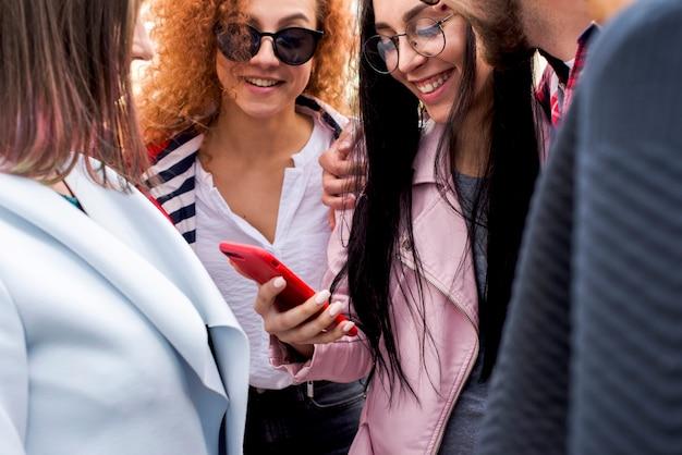 Gelukkige modieuze groep vrienden die het mobiele telefoonscherm bekijken