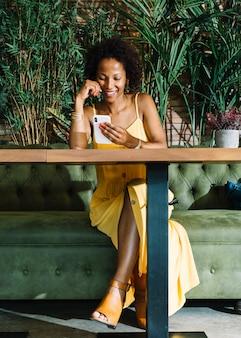 Gelukkige modieuze jonge vrouwenzitting in het restaurant die slimme telefoon bekijken