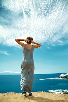 Gelukkige modieuze meisjesvrouw in toevallige hipsterkleding die zich op de klip van berg met haar handen achter hoofd op blauwe hemelachtergrond bevinden