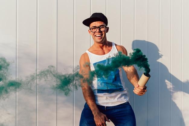 Gelukkige modieuze mens in oogglazen die een rookbom golven, die tijd doorbrengen