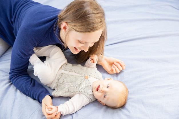 Gelukkige moeder die babymeisje bekijkt
