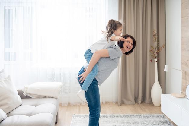 Gelukkige moeder die blije rit op de rug aan haar dochter geeft, die pret heeft thuis