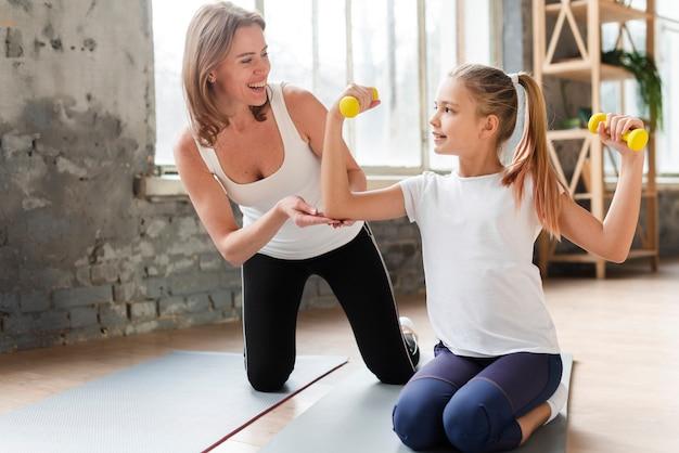 Gelukkige moeder die de gewichten van de dochterholding op yogamat helpen