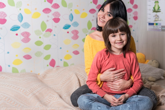 Gelukkige moeder die dochter van erachter op bed koestert