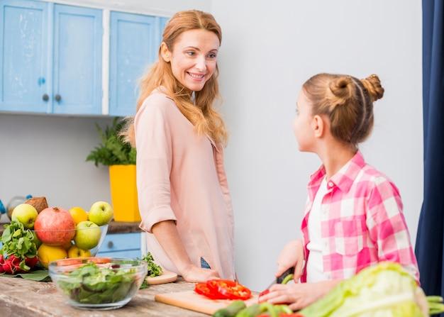 Gelukkige moeder die haar dochter bekijkt die de salade in de keuken voorbereidt